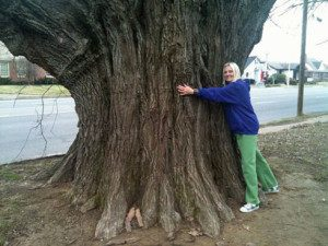 Janice Atkinson-Kiesel hugging a sassafras tree protected by a shotgun